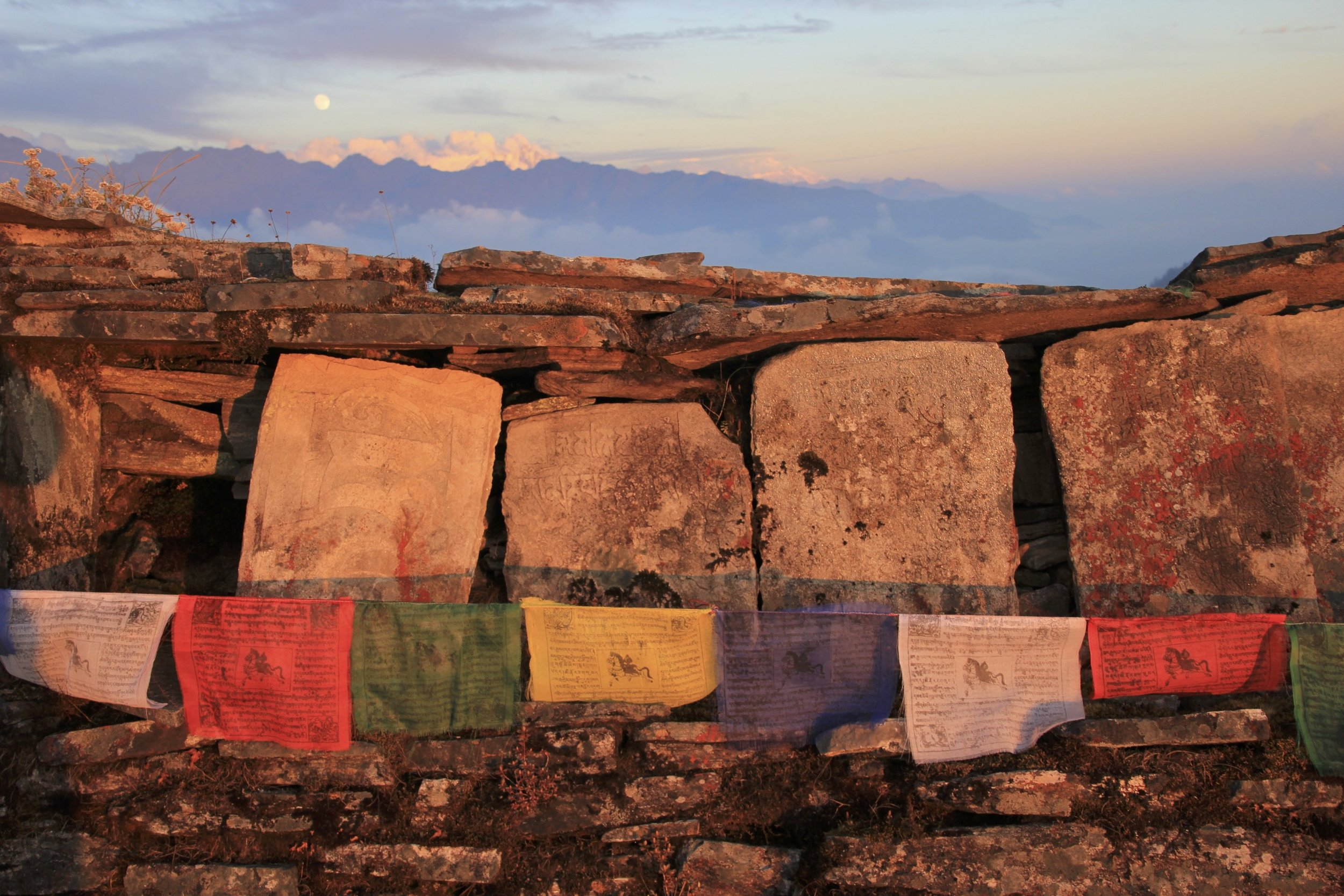 A mani wall and Buddhist prayer flags. Mani walls are walls built by followers of Buddhism. The walls consist of hand-crafted tablets inscribed with Buddhist prayers and images of the Lord Buddha.