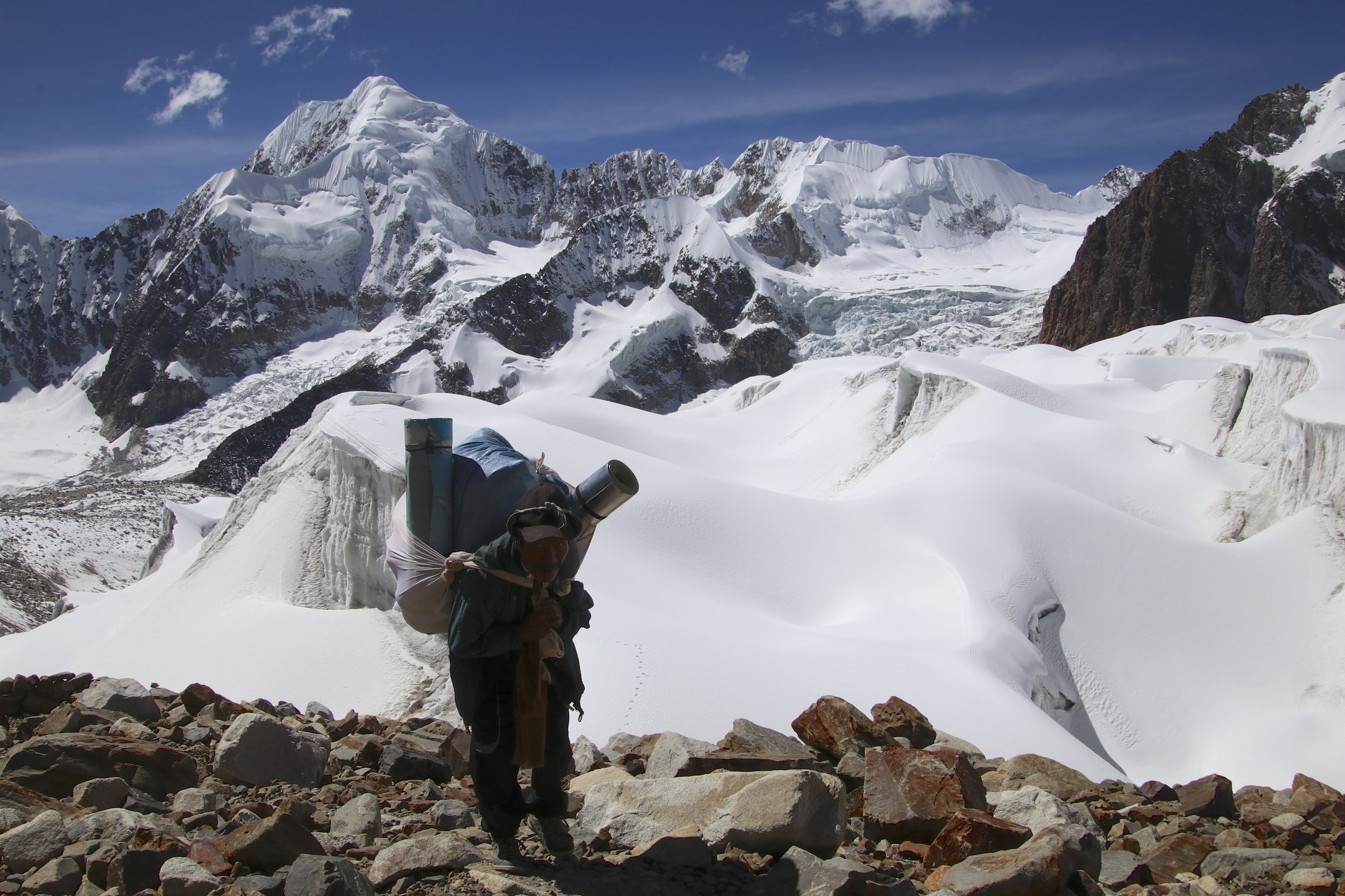 One of our porters approaching the high camp. Illampu is in the distance.