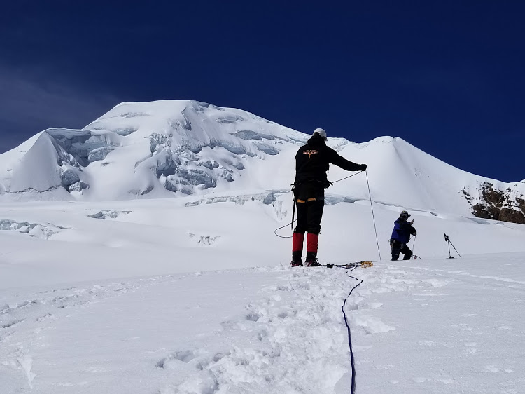 Working our way across one of the crevices with the summit bulk of Ancohuma behind.