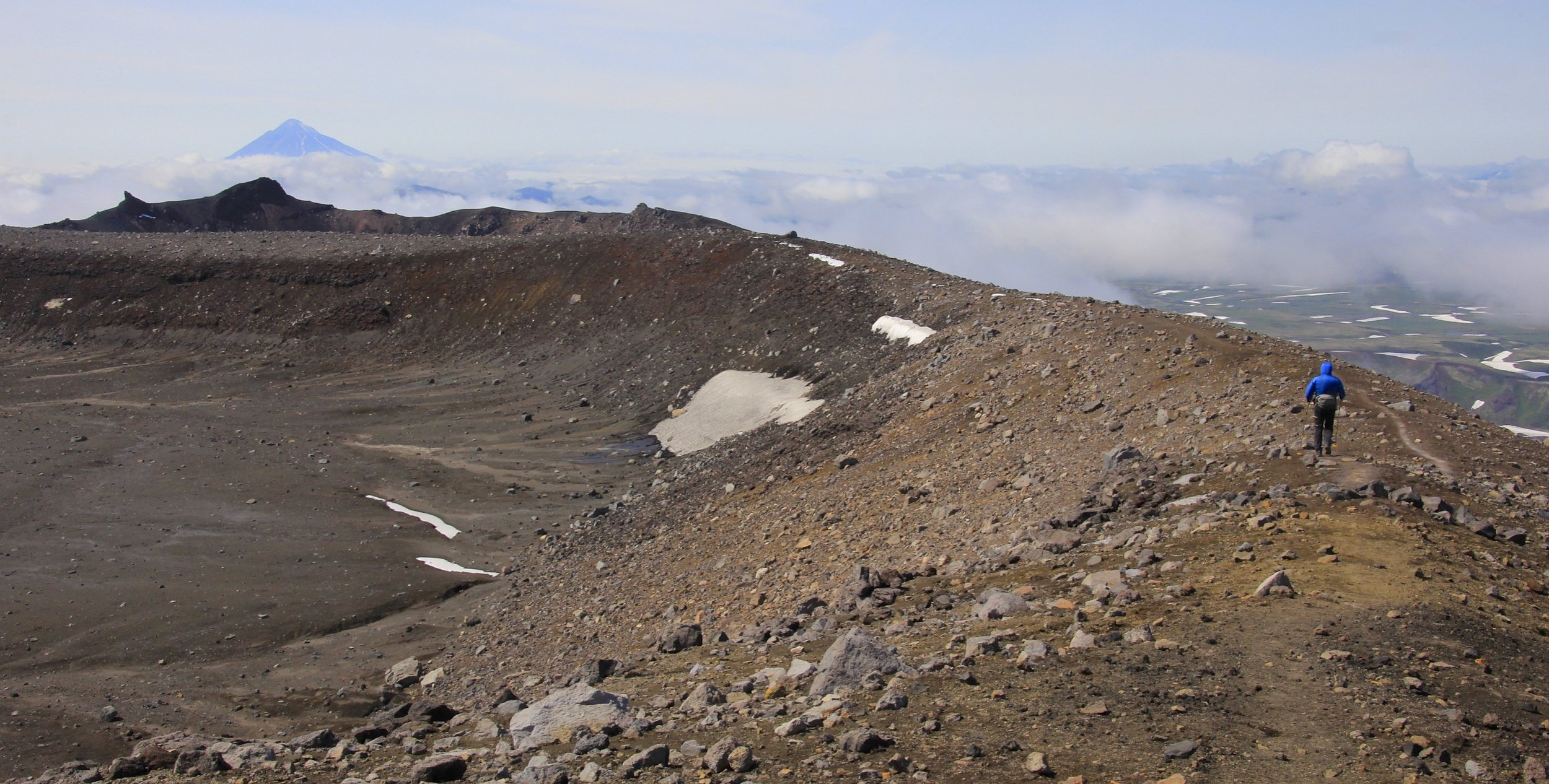 Walking on the rim of the Gorely crater with the Opala Volcano in the distance (2,475m).