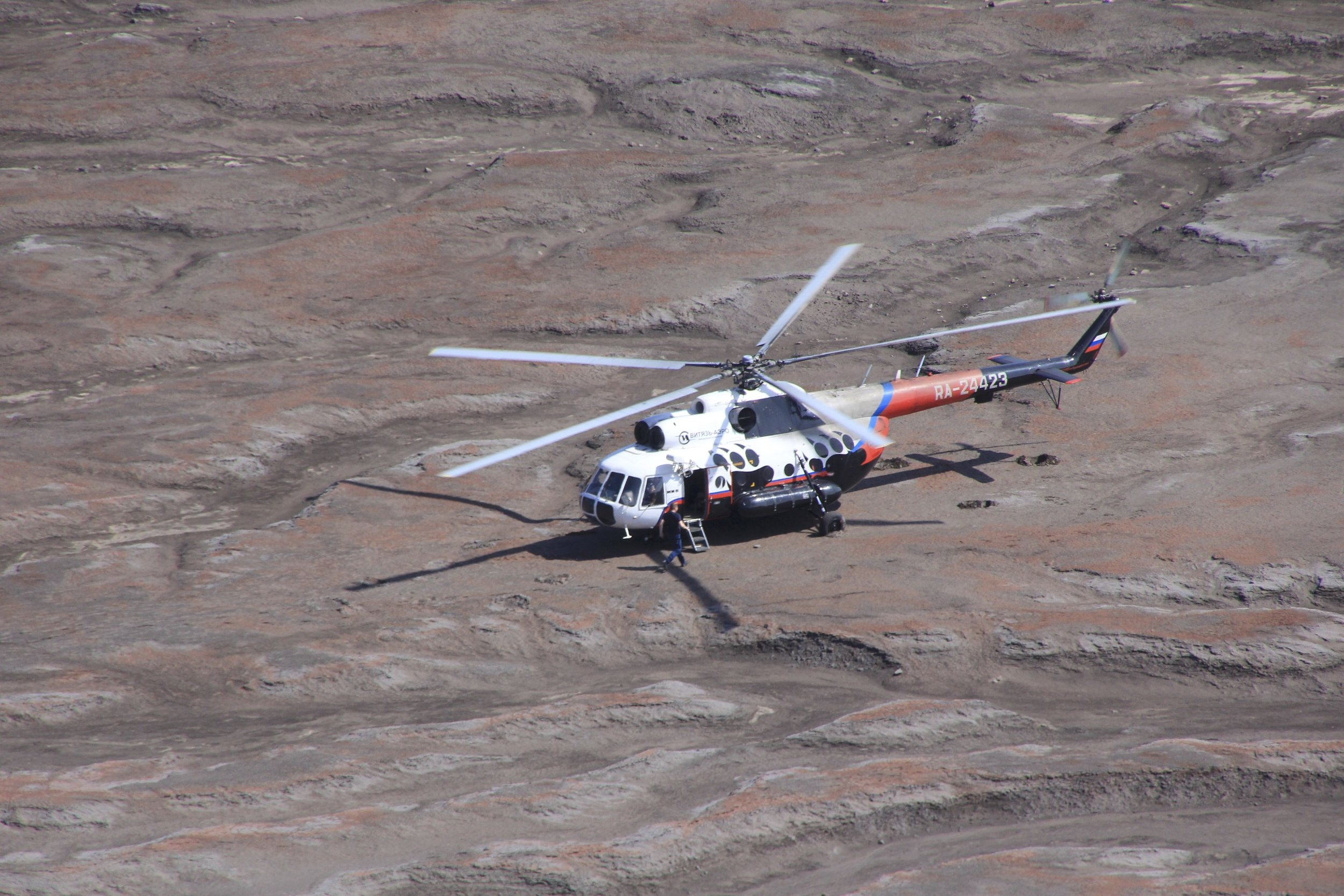 One can take a day trip to the Gorely crater from PK for around $700 US per person. The large Mi8 helicopter takes about 24 passengers. It has max cruising speed of 225km/h and a flight range of 900km. It is the most popular twin engine helicopter in the world. We observed their approach and landing. On the next photo, see the helicopter parked in front of the crater for scale!