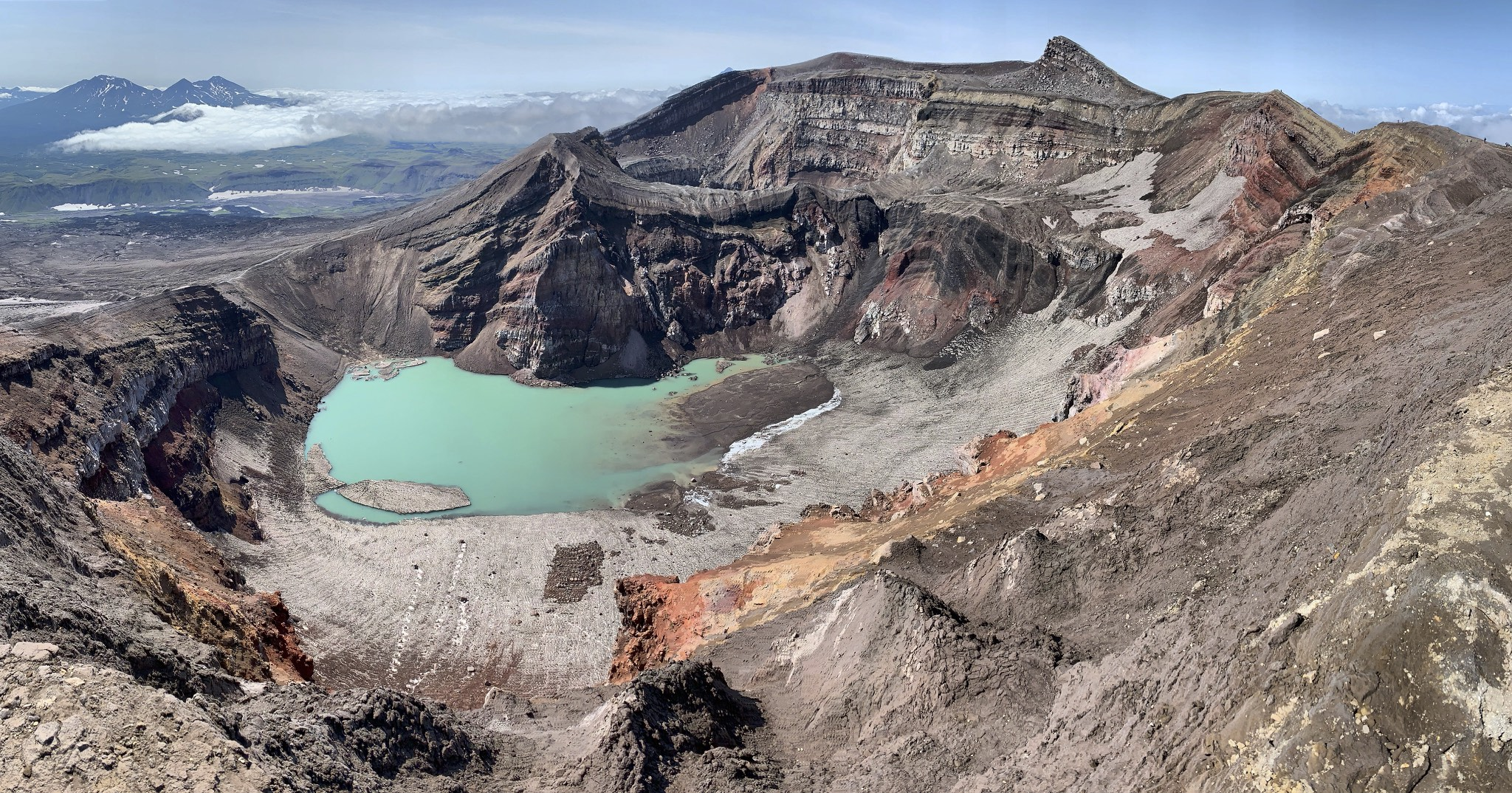 The main crater with a beautiful lake inside. The Gorely Volcano had 9 explosive eruptions in the past. Next to this lake crater is the eruptive crater with an active gas vent. The top of the mountain is the prominent fin in the distance.