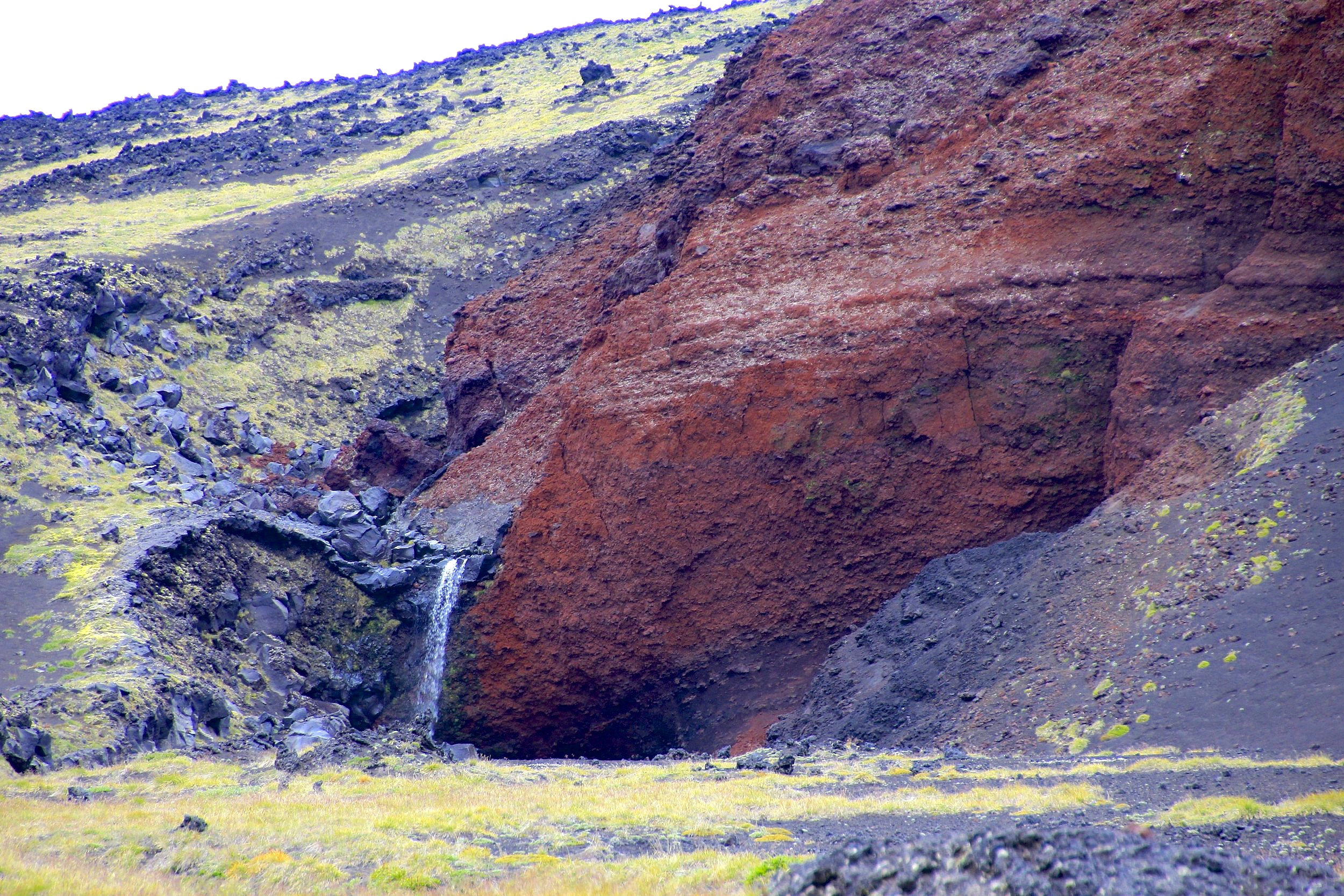 Small waterfall over red volcanic rock.