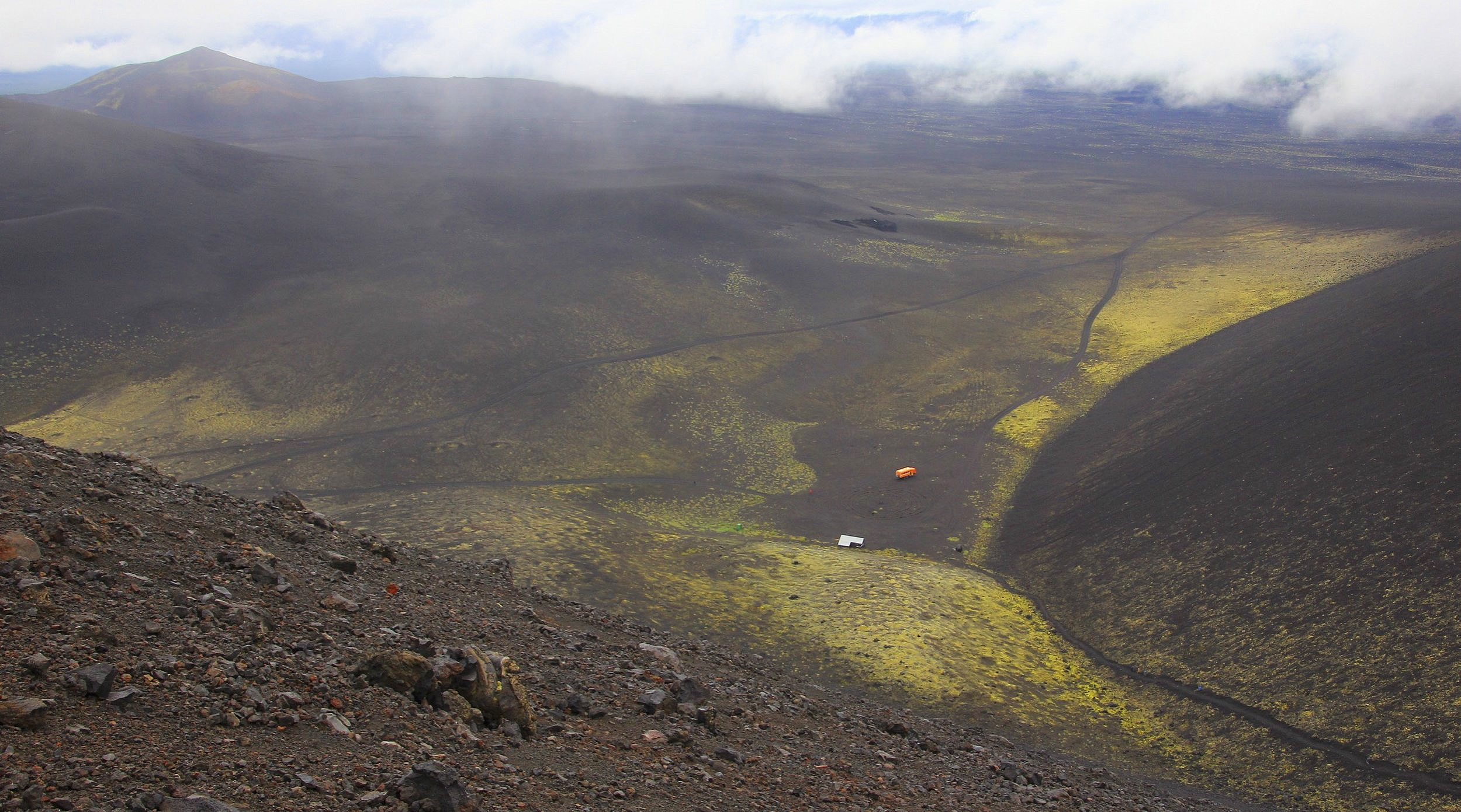 We were waiting for Sergei, our driver, and I hiked up to the top of a volcanic cone next to the shelter. From the top, the desolate landscape spreads out as far as the eye can see. I hiked to the top to warm up as we are getting really cold in the mist and rain.