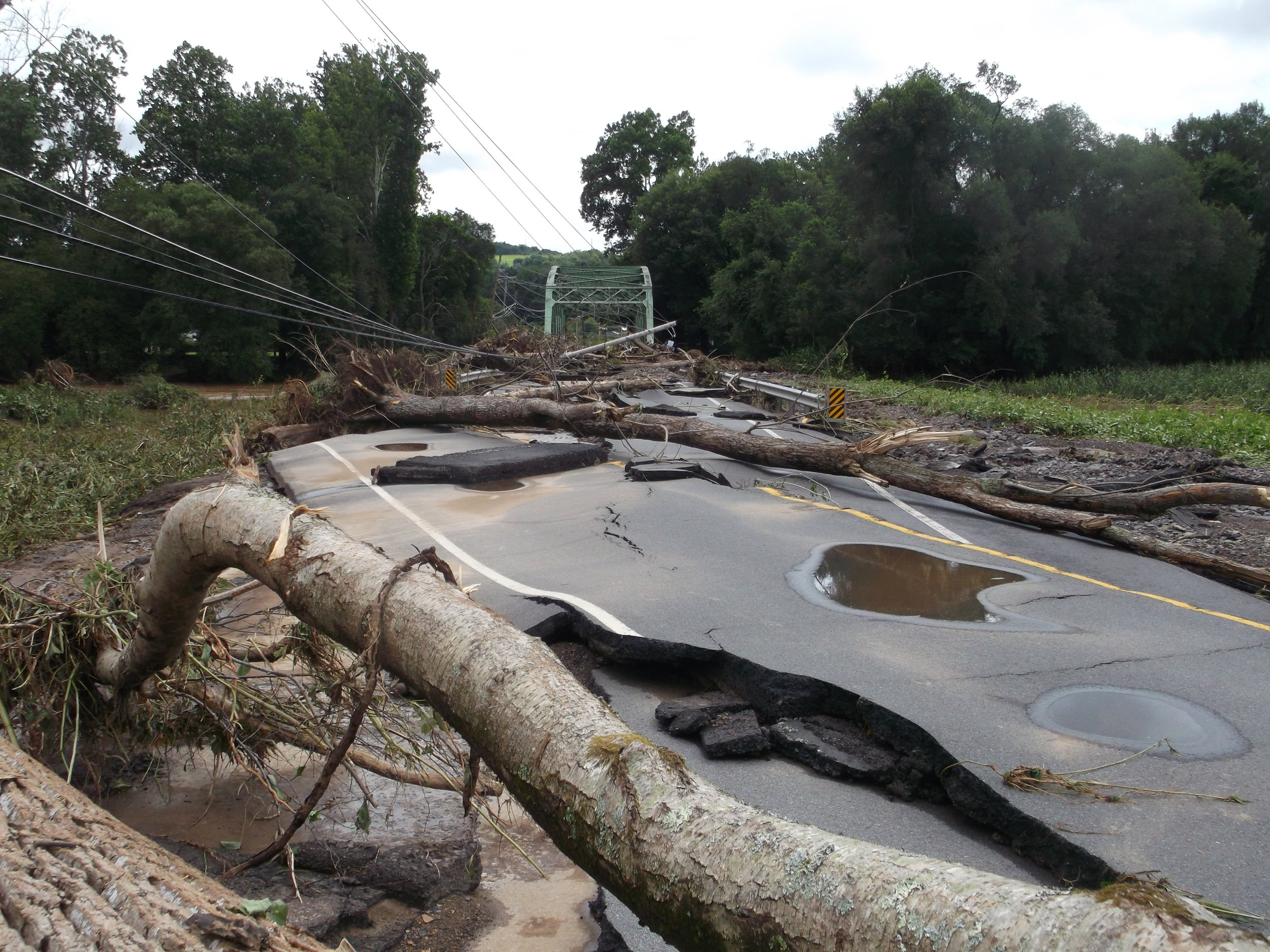 Power lines downed and sheets of asphalt roadway displaced by flood waters on Millville Road over Fishing Creek near Bloomsburg