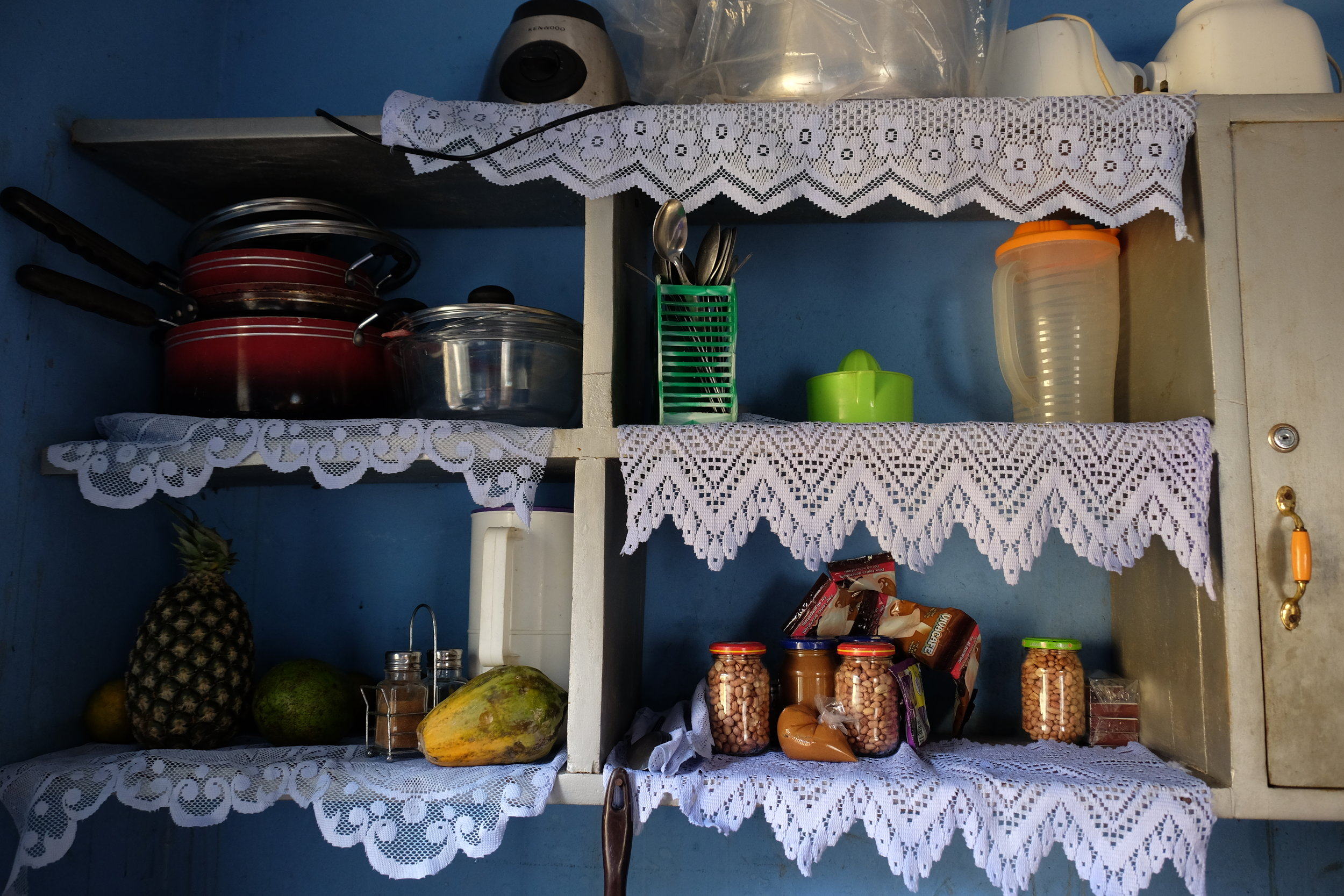 """Kitchen shelves. The peanuts that were roasted were jarred for snacks, or ground into """"paste"""" (aka, peanut butter) to be used in stews."""