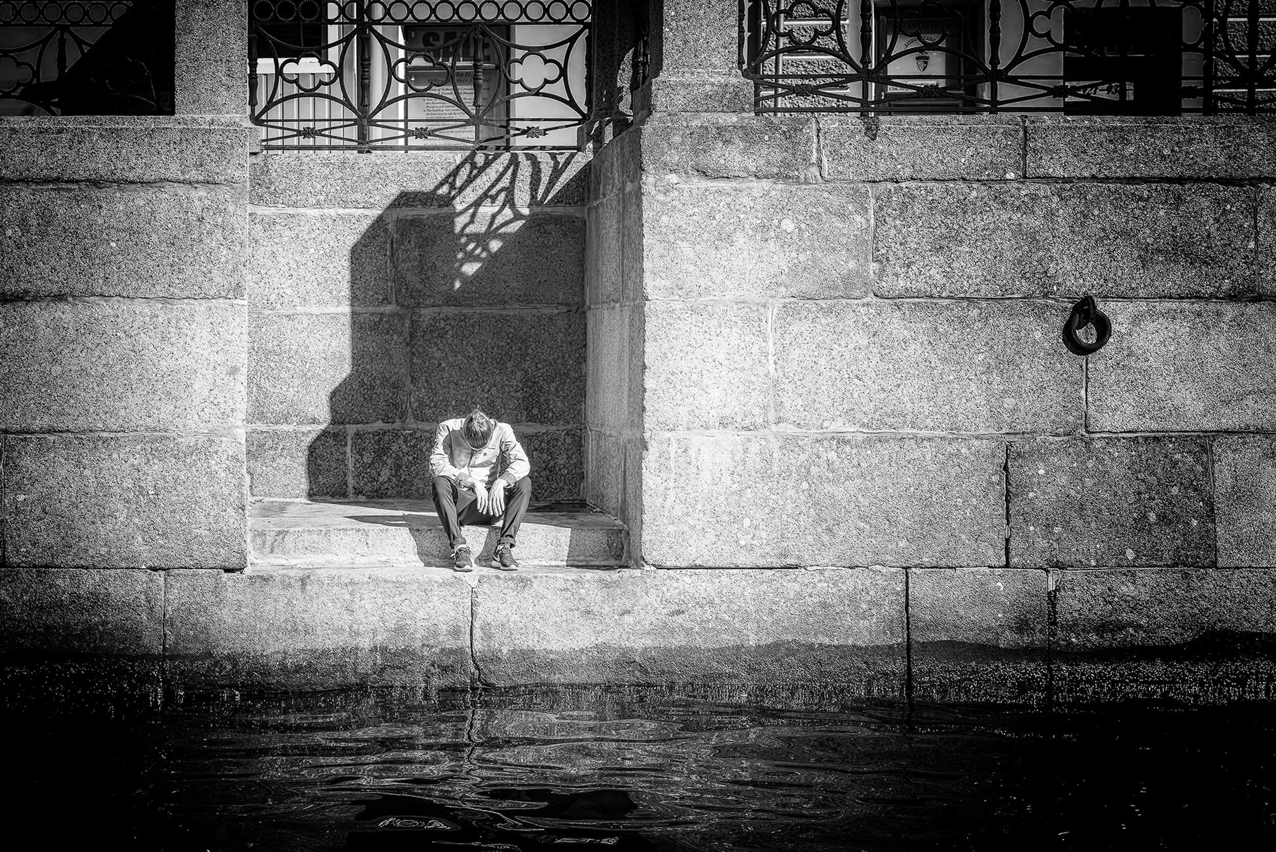 """Despair - Nikon D750, 1/100 @ f/4.0, ISO200, 120mm. Processed in Silver Efex Pro. This photograph was taken along one of the many canals in St. Petersburg, Russia. It was an early morning shot, so I'm guessing this guy had a tough night. See the poem """"I Often Think of the Color Black"""" in the Poetry Section."""