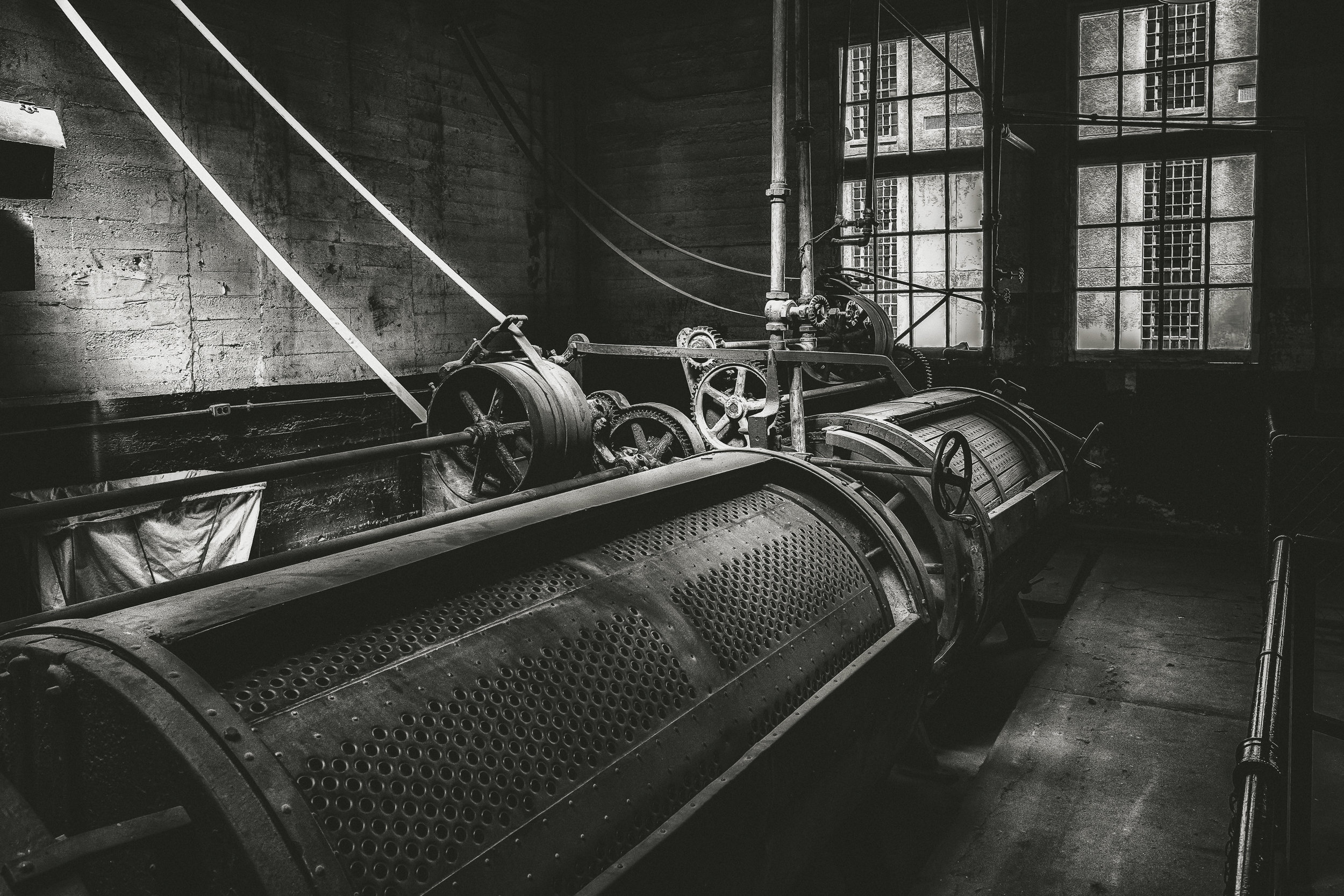 The Machine - Fujifilm X-T3, 1/125 @ f/8.0, ISO 400, 16mm. A prison laundry facility turned museum. Shot at the Old Idaho State Penitentiary. I particularly like how the light emanating from the upper left corner illuminated the machinery.