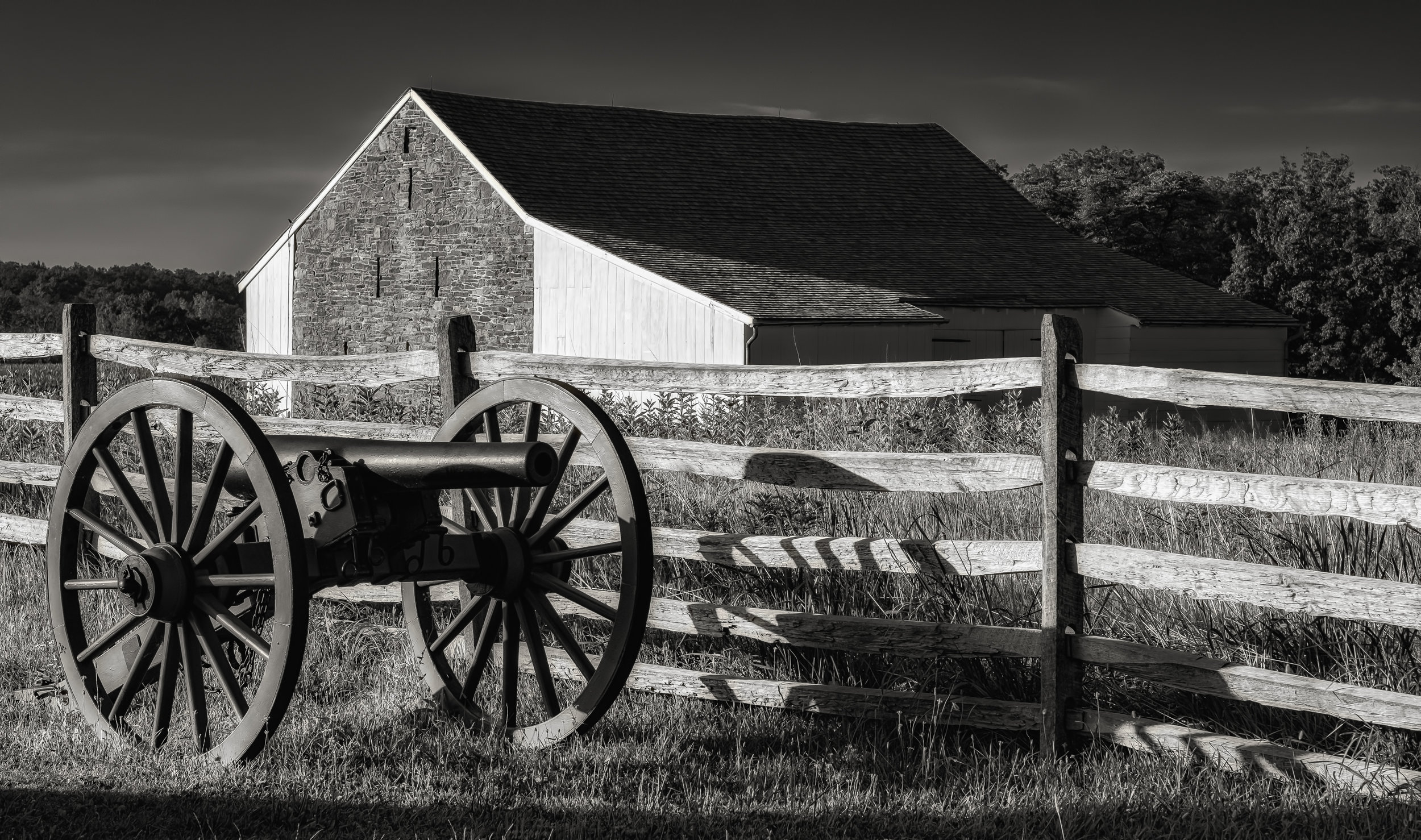 """Gettysburg Dream - Fujifilm XT-3, 1/500 @ f/8.0, ISO 160, 56mm. An early morning shot of the McPherson Barn on the 1st day's battlefield at Gettysburg. The light and shadow called for a black and white toning. The cannon, fence and barn make for a strong composition. This pic is one of my favorites from a recent visit. I have been to Gettysburg more times than I can remember and I encourage all to visit. It is truly """"a vision place of souls."""" See the poem by the same title in the Poetry Section."""