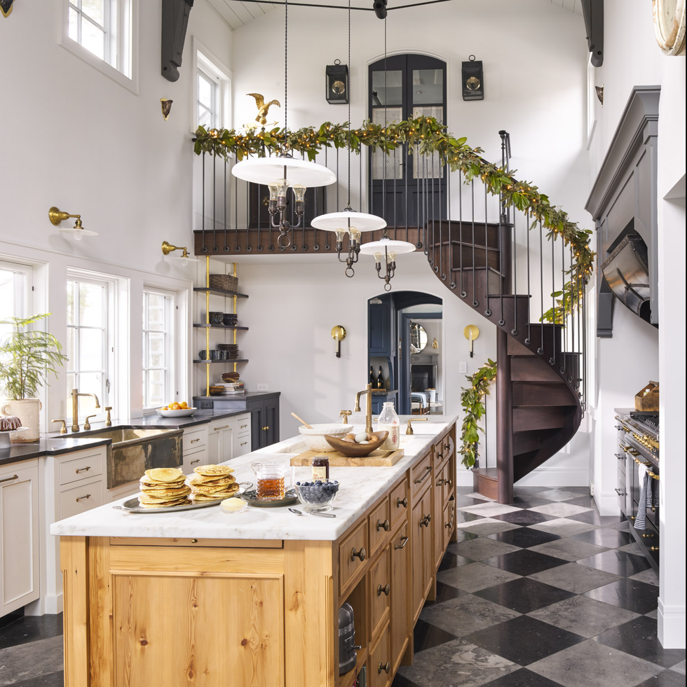 This kitchen space absolutely took our breath away. The spiral staircase commands the room, leading down to an open and airy kitchen. Design by  Cathy Chapman  | Photography by  Annie Schlechter