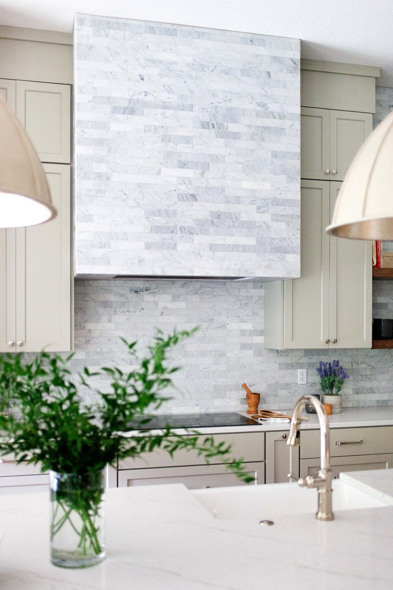 The polished nickel faucet and cabinet hardware are the perfect accent for the gray and blue tones of the marble tile.