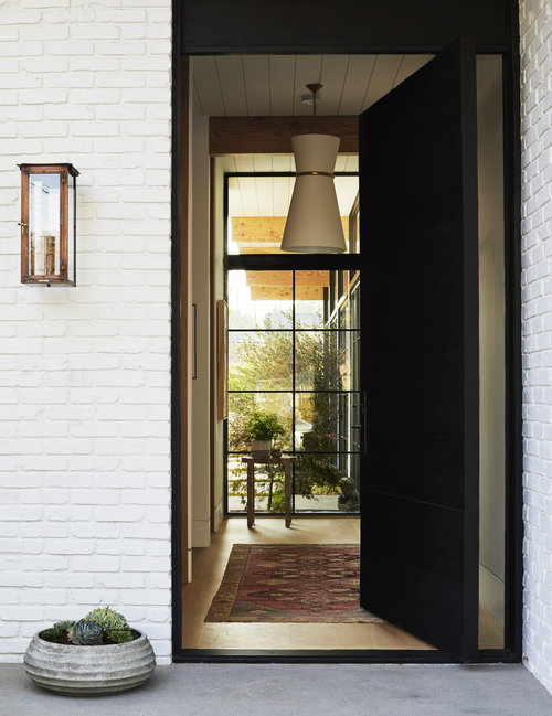 The dark-toned front door is beautifully contrasted by the exterior of the home, which practically begs you to enter. The white lighting fixture placed in the entryway paired with the vintage rug create an inviting environment, while also drawing the eyes to the view out of the full-length windows.