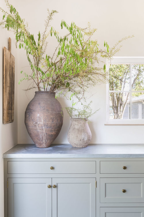 A corner of the kitchen is simply styled using weathered pottery and a rectangular cutting board. (Photography by  Alyssa Rosenheck )