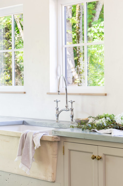 The large farmhouse sink with nickel faucet fixture is placed below the windows, providing a stunning view of the outdoors. (Photography by  Alyssa Rosenheck )