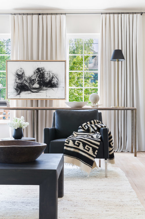 Vertical elements like this black shaded lamp and tall, skinny windows draw the eyes upward, exaggerating the illusion of a larger space. (Photography by  Alyssa Rosenheck )
