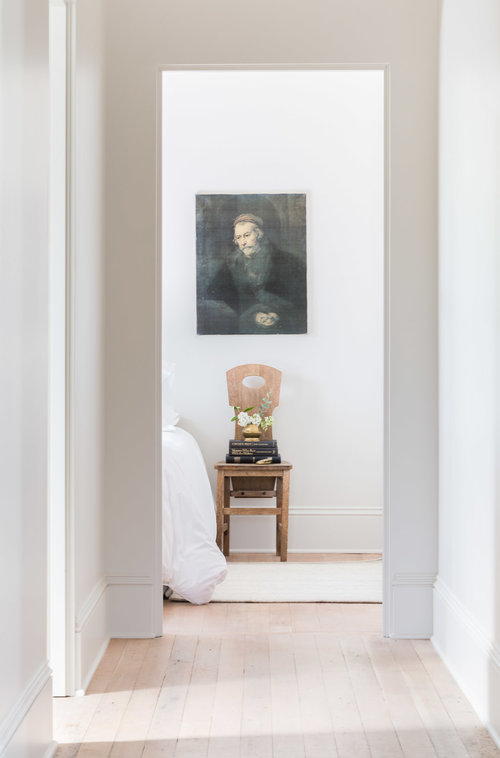 Looking into the bedroom, a timeless print rests above an old schoolhouse chair. (Photography by  Alyssa Rosenheck )