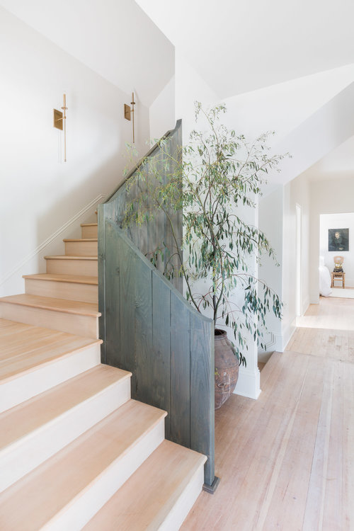 Vertical, fence-like railing frames a bleached wood staircase. (Photography by  Alyssa Rosenheck )