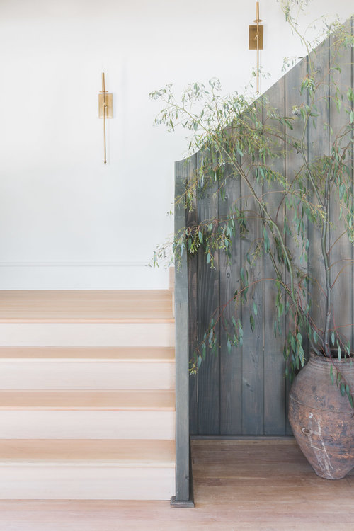 Thin candle sconces, antique ceramic vase, & vertical fence-like railing create a chic, yet rustic entry area. (Photography by  Alyssa Rosenheck )