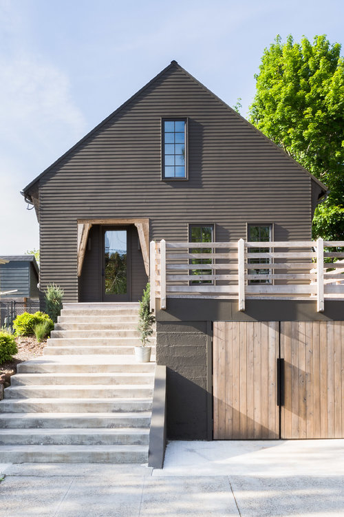 A simple, yet charming exterior with a below-grade garage and horizontal fencing around the deck. (Photography by  Alyssa Rosenheck )