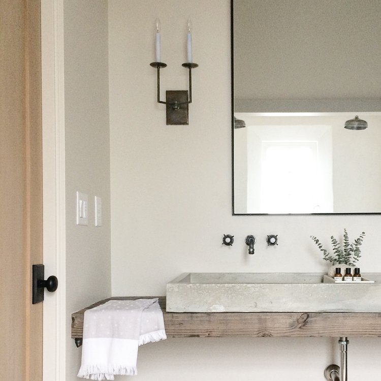 Concrete sink basin over a wood slab counter, light wood door with clean black hardware, old school sink faucets, candle sconces featured here in the home as well, this lighting choice brings a pre-electricity, old school vibe to the home which takes you back to the simpler times. (Photography by  Alyssa Rosenheck )