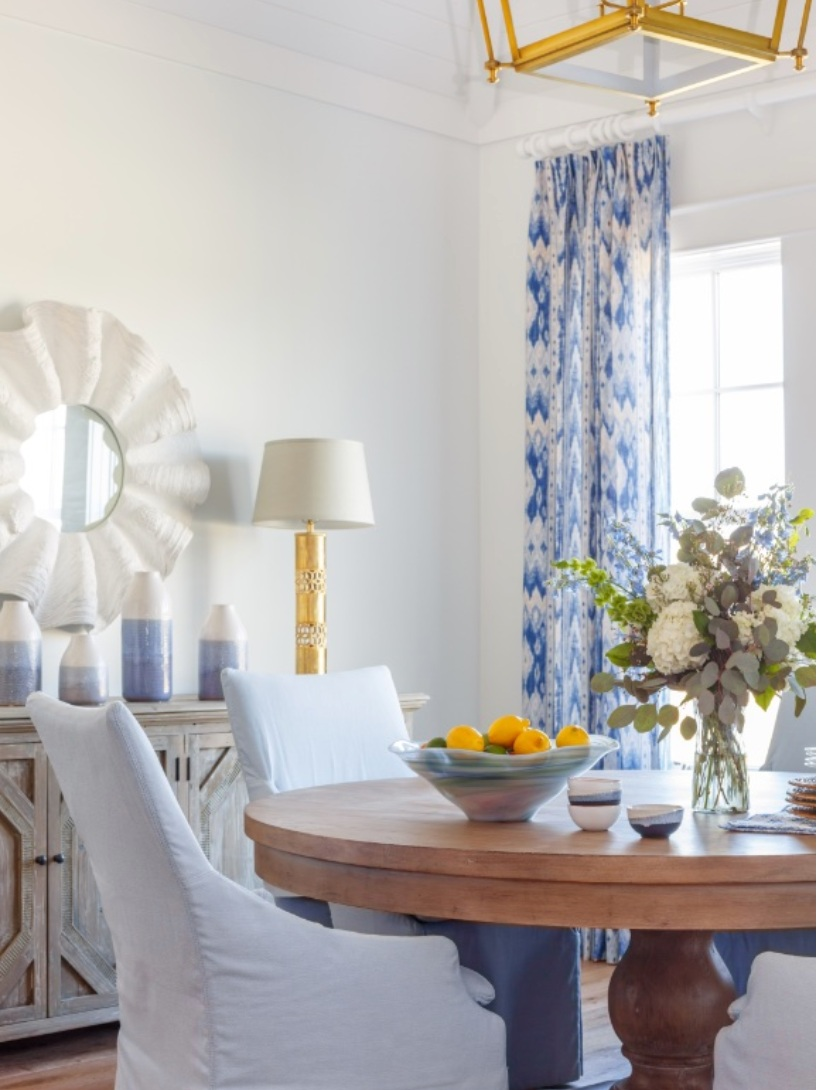 A round wooden dining table centering the space is styled with a bowl of fruit and florals.