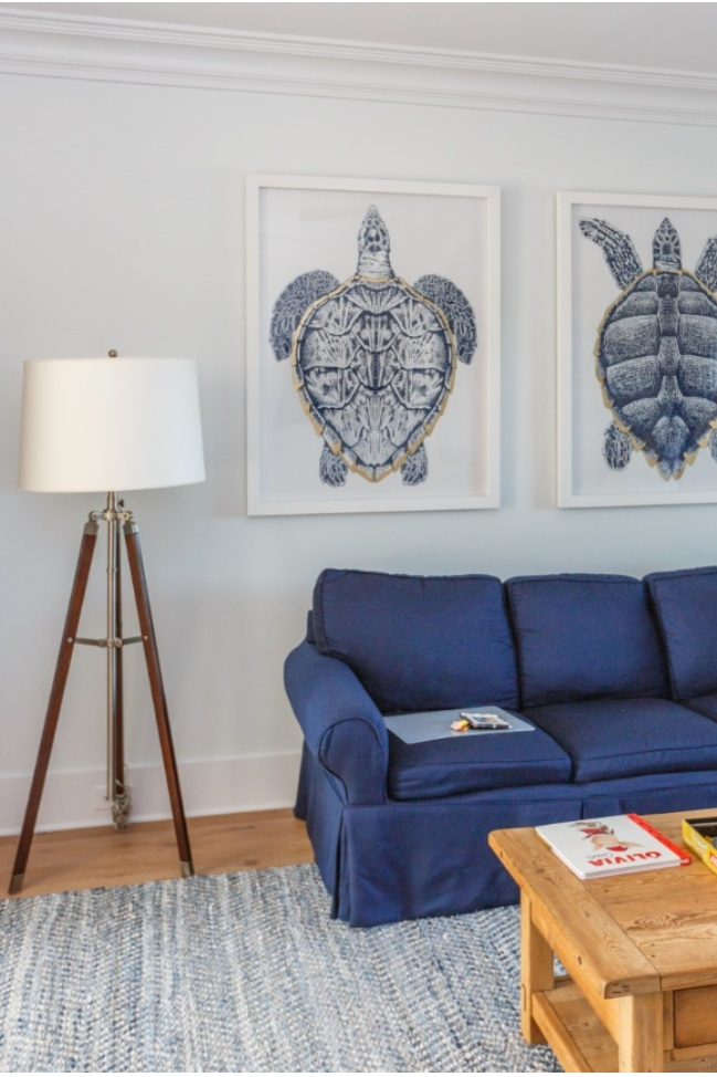 A tripod floor lamp and oversized turtle prints line the room.