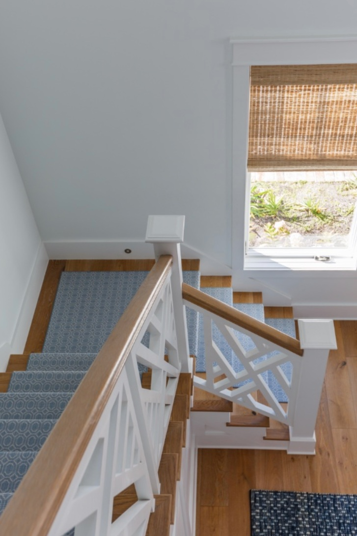 A muted blue runner adds comfort and functionality to this wood and white staircase.