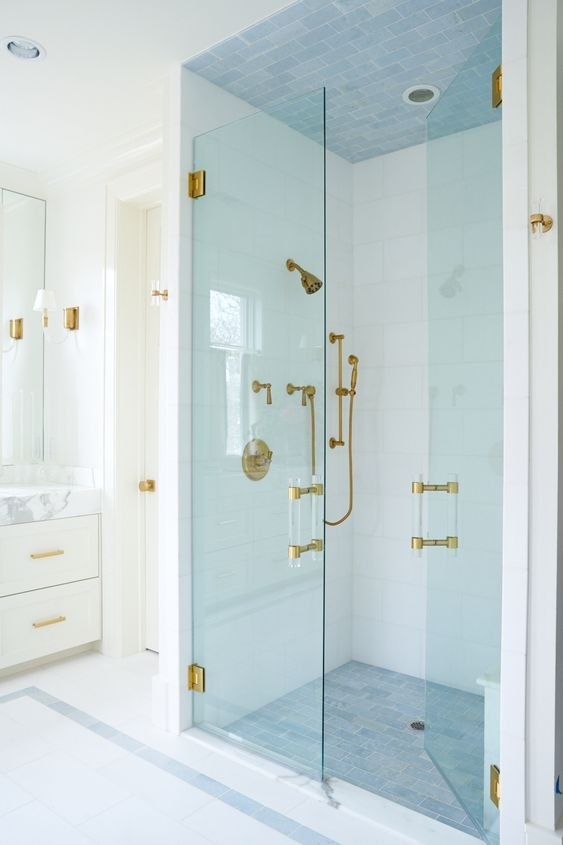 A glass front shower beautifully reveals accents of gold hardware.