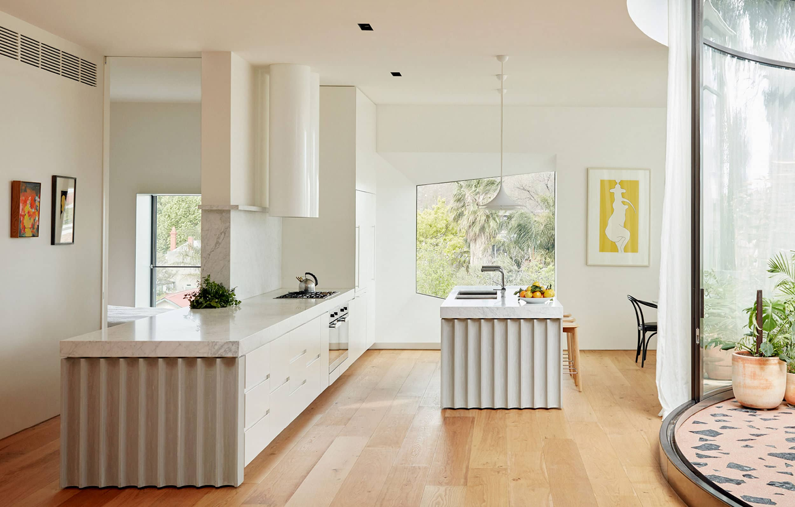 Design by  Anon Studio  | Photography by  Tom Ross  &  Freadman White  A fluted touch to the cabinetry and kitchen island are right at home amongst terrazzo, white lighting, and sleek, hardware-less cabinetry.