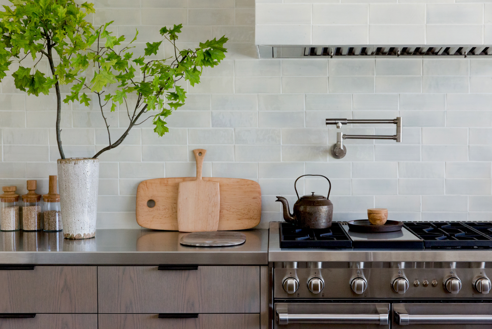 """A closer look reveals a double stacked tile backsplash and matching range hood. By changing the traditional """"brick stack"""" of the tile just slightly, so much visual interest is added! Speaking of unique details, this stainless steel countertop defies tradition and brings a touch of masculinity to the room."""