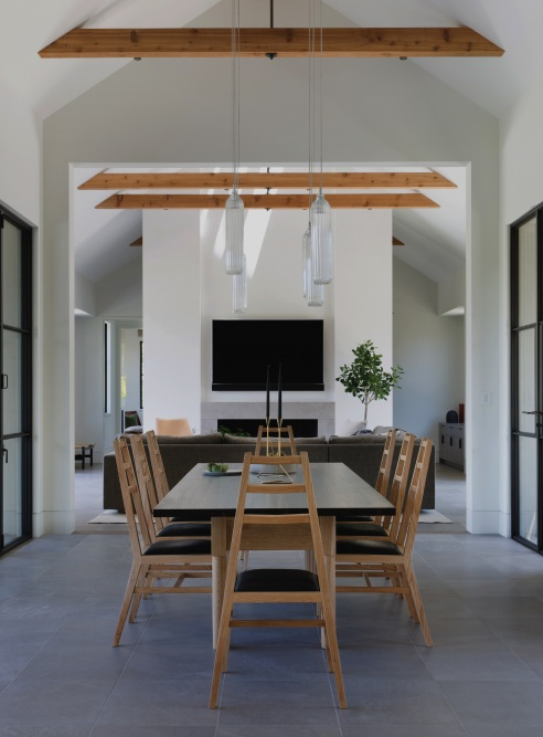 A-frames all the way | A second dining area in the home opens up to the living room, which also features a vaulted ceiling. These A-frame dining chairs seem to fit in perfectly!
