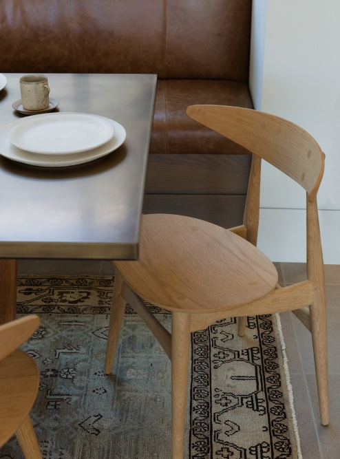 Mid-century modern meets old-schoolhouse | These wooden dining chairs are the perfect compliment to the rich, leather bench and vintage rug.