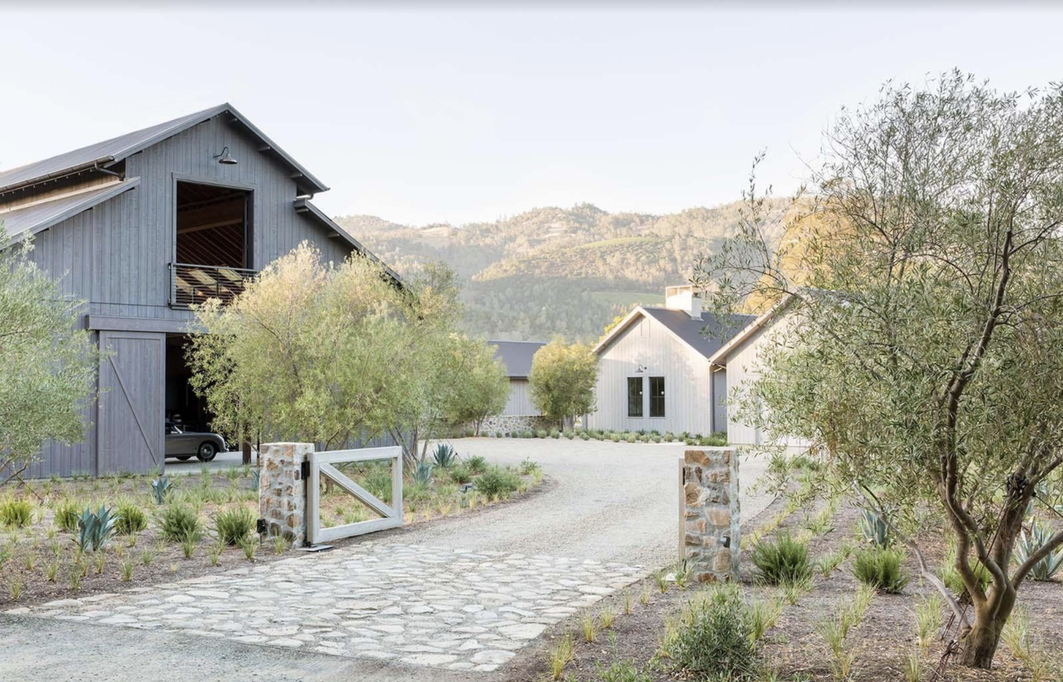 A welcoming entrance to the property is created using a simple stone and wood gate. As you look around, you'll quickly notice that the spacious plot of land this home was built on includes not only an attached garage, but also a two-story barn for added storage. Both structures are cladded vertically, softening the facades and adding to their visual height. The designers and builders of this project collaborated with a dedicated landscaper to complete the stunning greenery surrounding the home which perfectly compliments the backdrop of rolling hills.