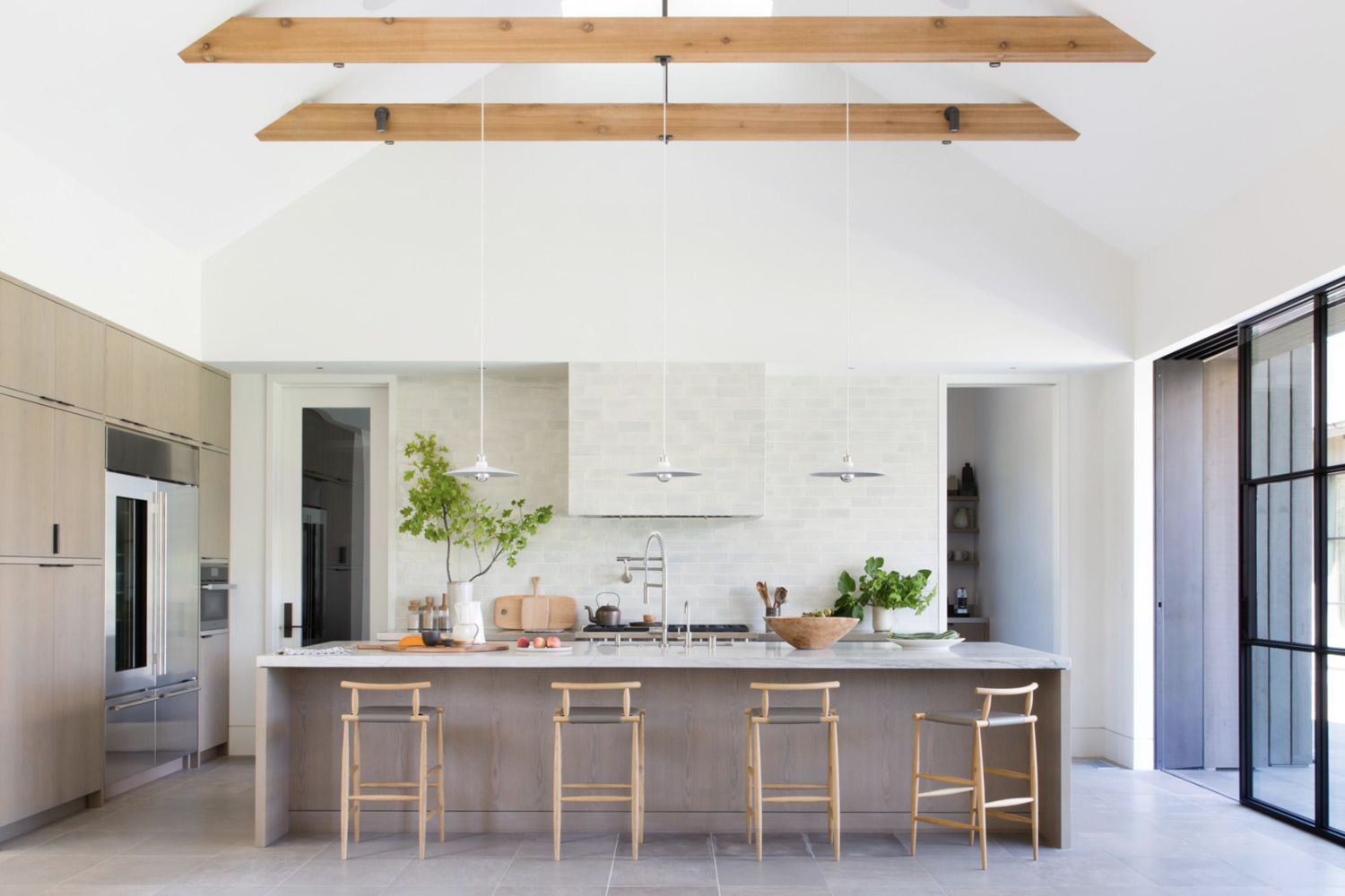 A large kitchen with loads of natural light greets you upon entering the home. Its sky-high vaulted ceiling is adorned with large exposed beams from which a trio of sleek pendants are hung.