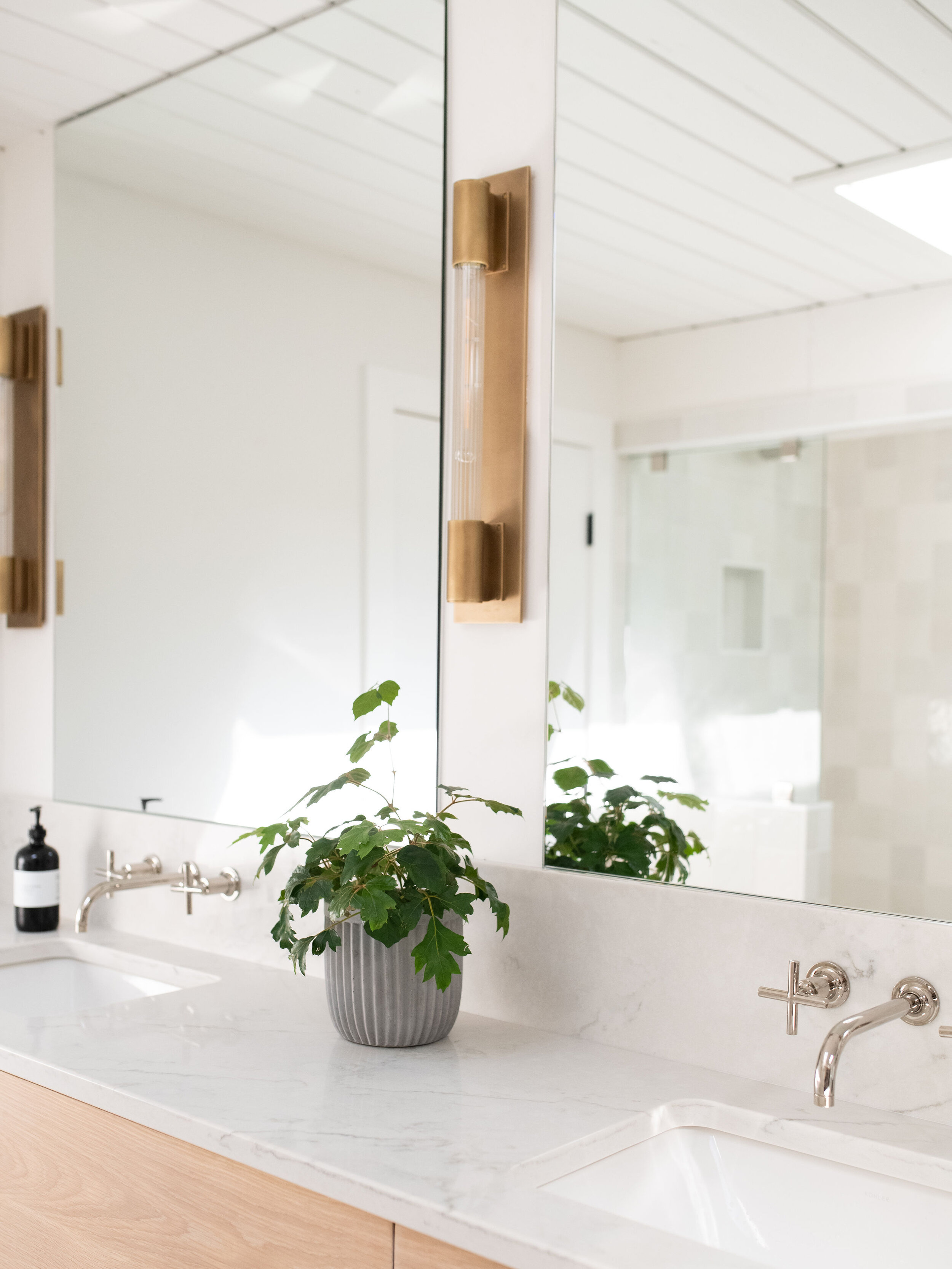 These eye-catching wall mounted faucets are modern, sleek, and the perfect accent to the brassy sconces above