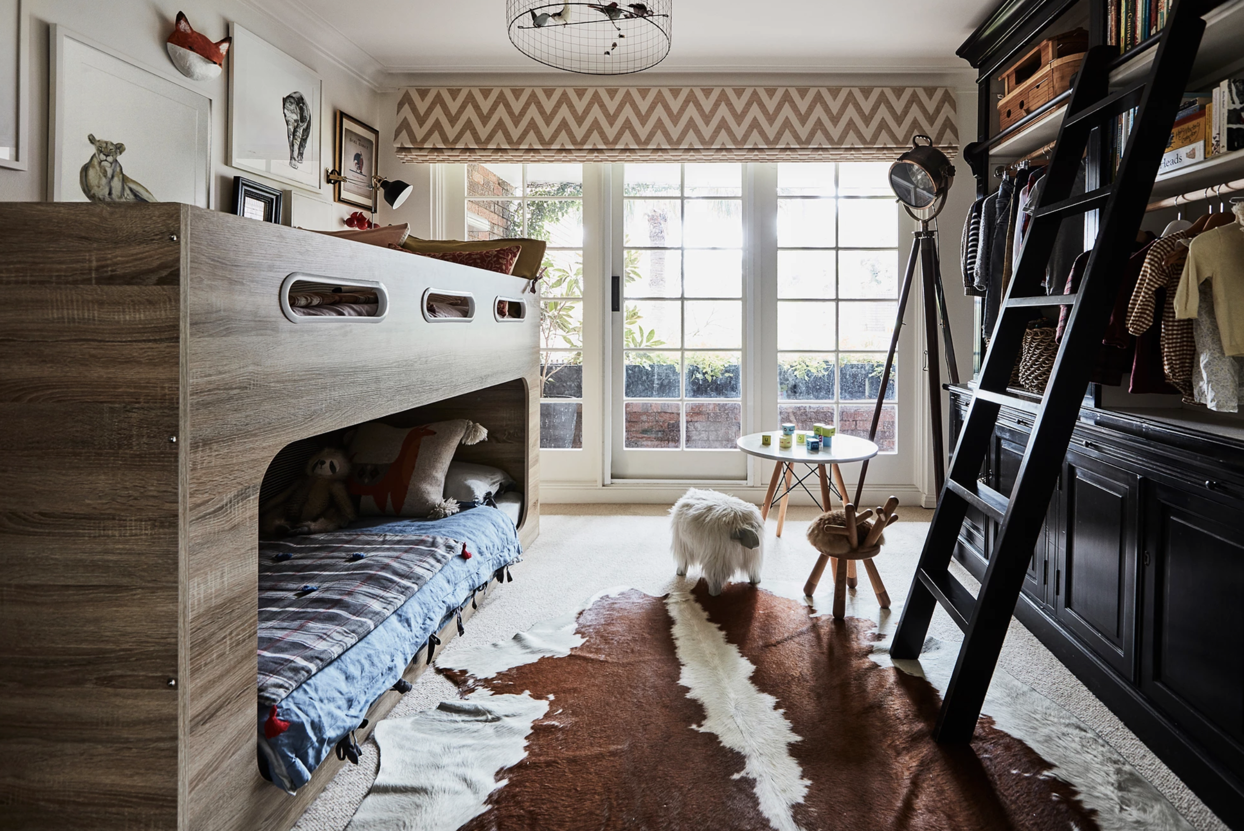 This small bedroom is jam-packed with architectural detailing and kid-friendly knick-knacks. Fun prints like the window treatment and quilts bring life to this space, and floor-length windows flood in so much natural light!