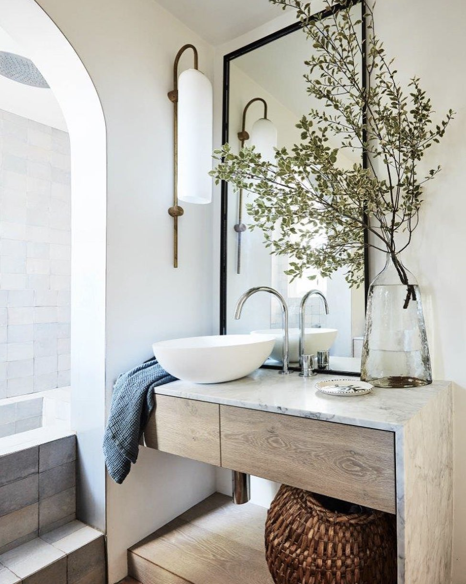 Waterfall counters, handmade Portuguese tiles, and a lengthy wall mirror create a serene atmosphere.