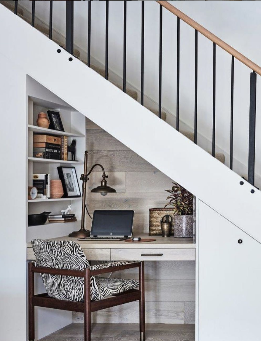 Space beneath the stairs is maximized with a small workspace, complete with niche shelving and a fun zebra-print chair! The cladded oak wall ties this hidden gem in with the rest of the main living area.