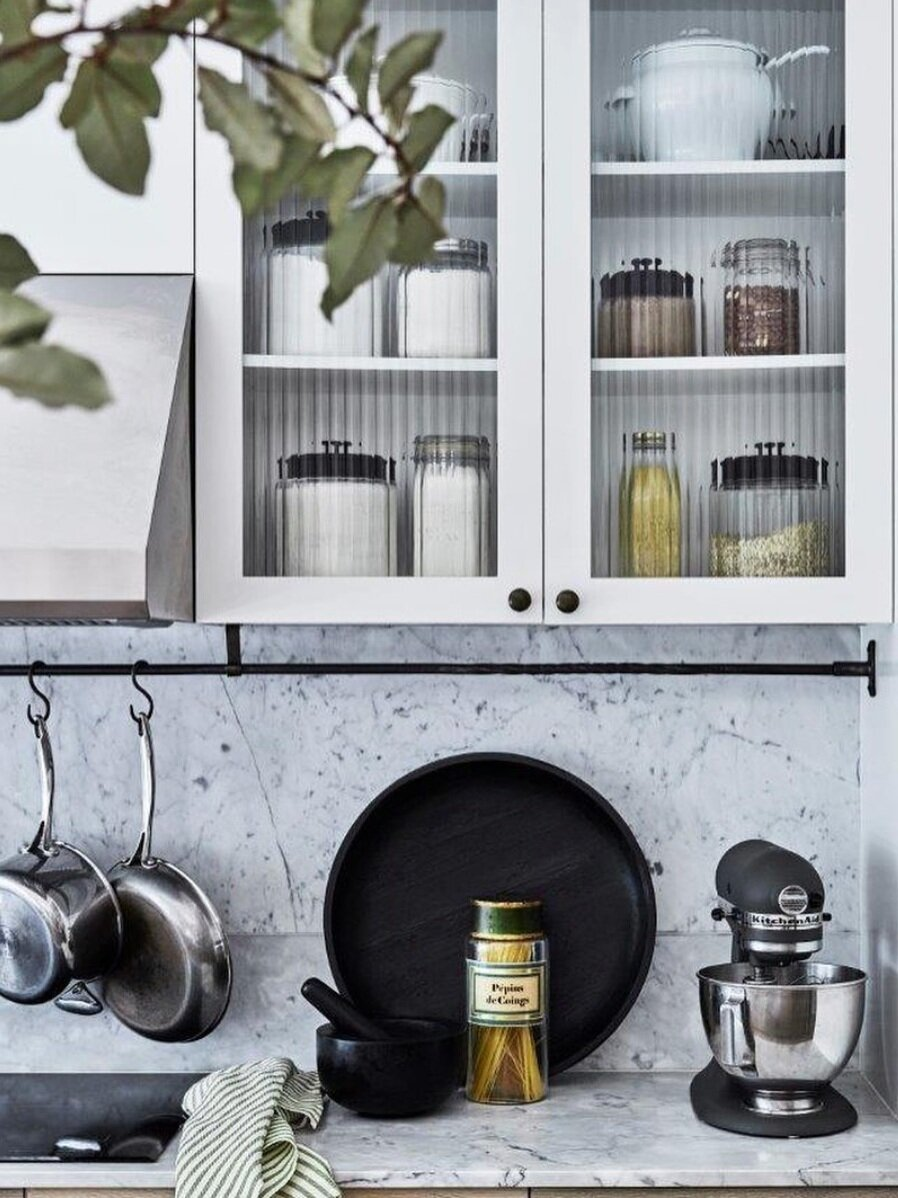 Fluting is also used in the these cabinet doors to partially expose the contents behind, while adding rich texture to the kitchen's prep space.