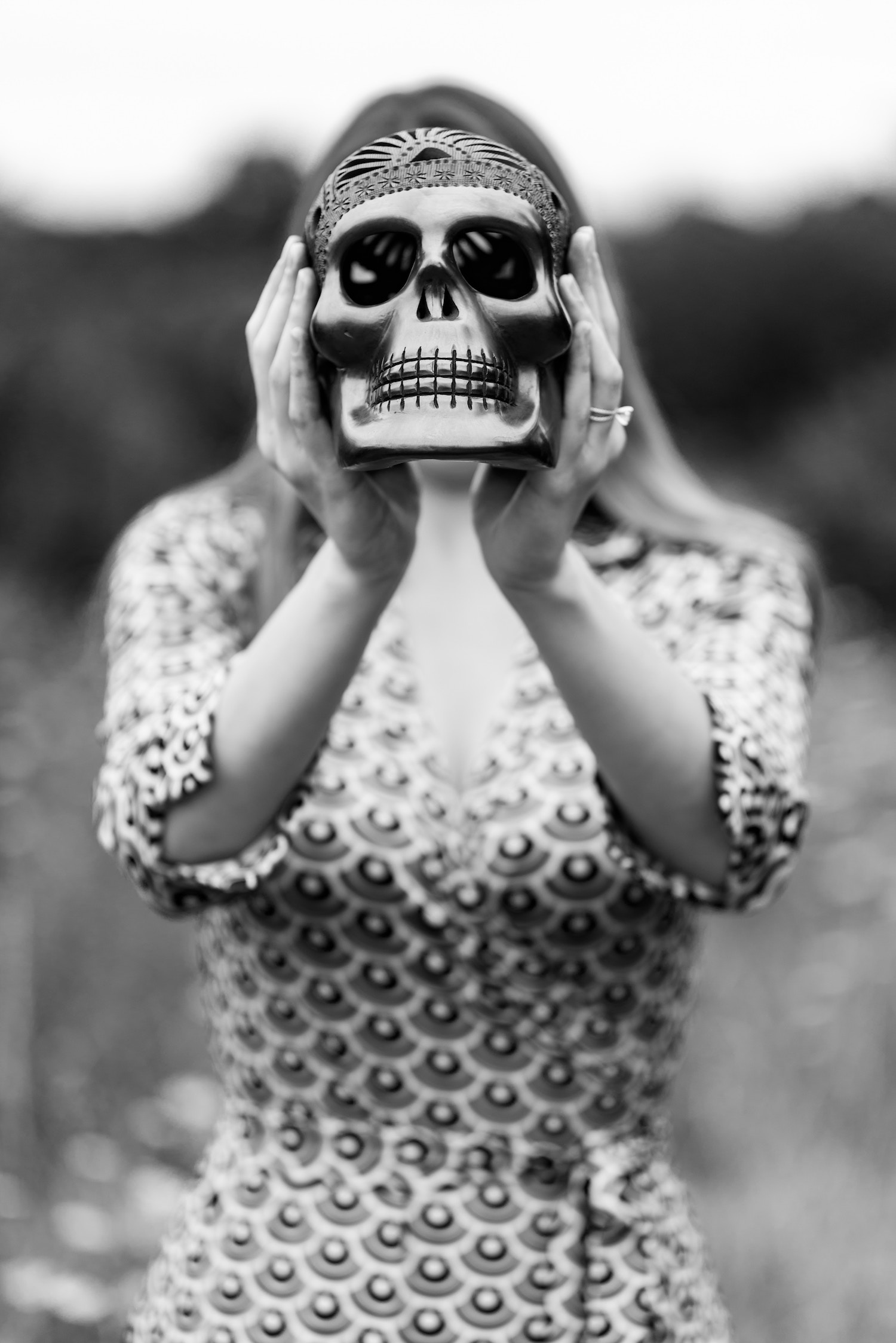 Explore your Mind, Manchester Psychotherapy - Black and white photo of a woman in a patterned dress holding a silver skull up in front of her face