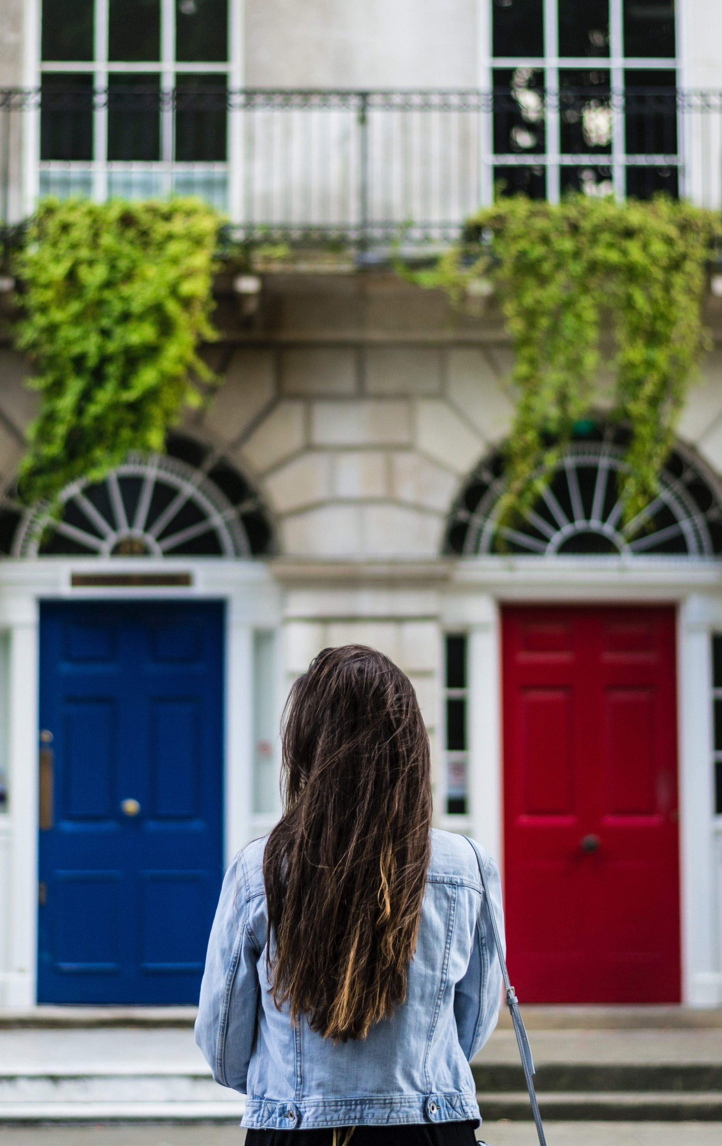 Explore Your Mind: Woman with dark hair standing in front of two doors; one red and one blue.