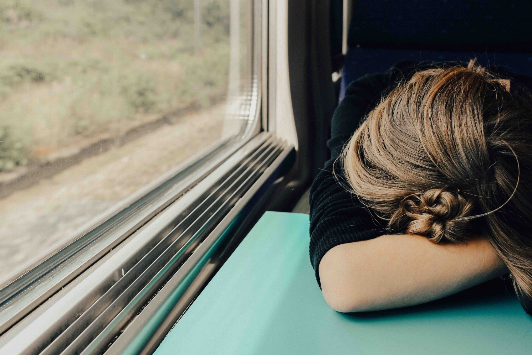 Explore Your Mind: White, brunette woman on a train, with her head resting on a blue table