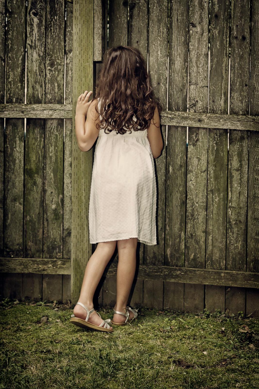little girl peeking in the fence-Edit.jpg