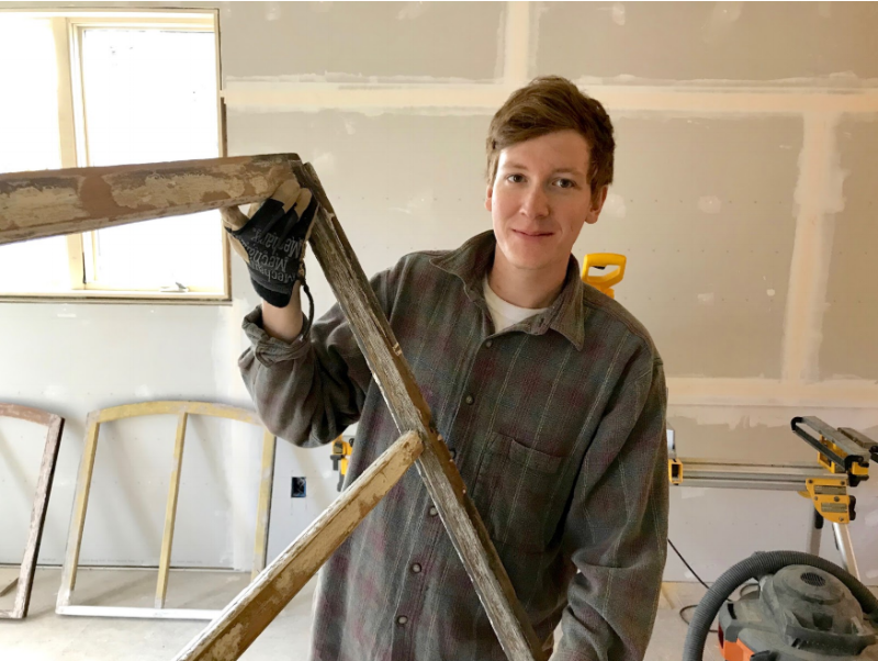 Hunter works on the restoration of wood windows from a house built in 1880.