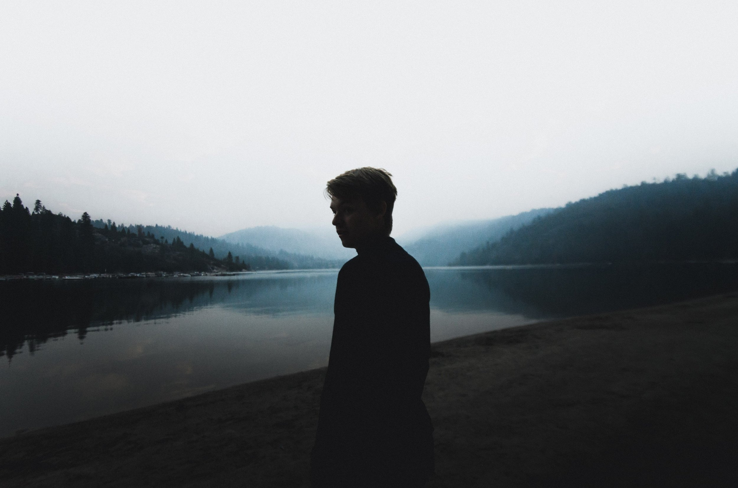 silhouette of man by water with mountains in background
