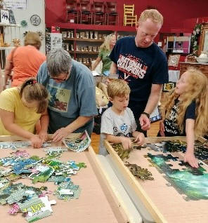 Families teamed up to solve puzzles, individuals worked while their friends gave pointers, and small children found joy in seeing the pieces come together to make a bigger picture.