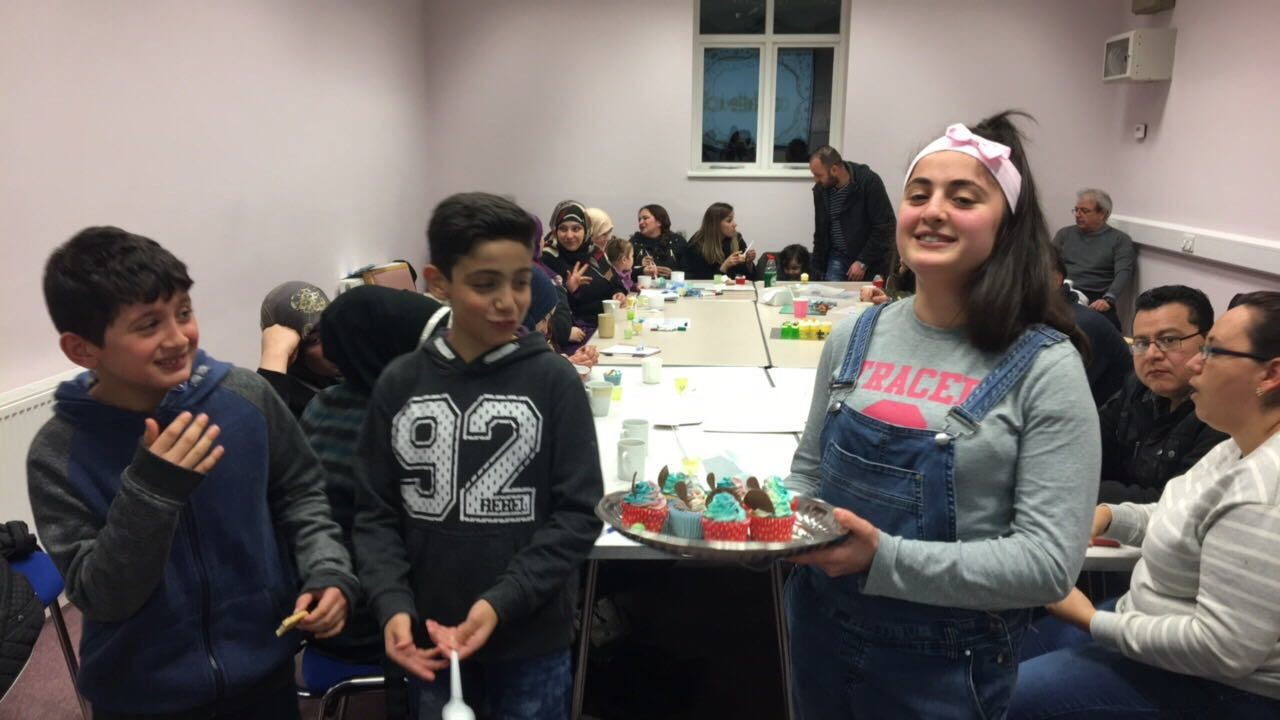 Children with cakes donated from Bake for Syria during adults' English conversation classes