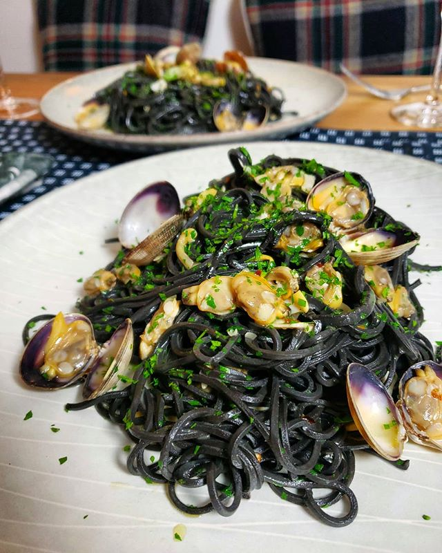 Squid ink chitarra alle vongole. Handmade fresh pasta dyed black with cuttlefish ink (not actually squid), clams, garlic, wine, red pepper flakes 🦑🖤🍝 . I first learned to make this dish from @seriouseats. Although the base recipe is not complicated, they do such a good job of finding at least one clever way to improve upon a classic. In this case @dgritzer likens a surplus of shells to serving rocks and suggests pulling the clams from their shells, saving a few for garnish. . At first glance it might look like spaghetti, but look closely and you'll see the pasta has sharp right angles whereas spaghetti is tubular. It's so squidgy in your teeth when you eat it! My favorite long pasta shape. . . . #squidink #pasta #freshpasta #clams #seriouseats #seasonofsalt #feedfeed #instafood #buzzfeast #foodandwine #eater #food #beautifulcuisines #yummy #yum #dailyfoodfeed #f52gram #instapic #thekitchn #homemade #foodie #EEEEEats #foodgasm #onthetable #eater #forkyeah #foodbeast #eatmunchies #tastingtable #lifeandthyme