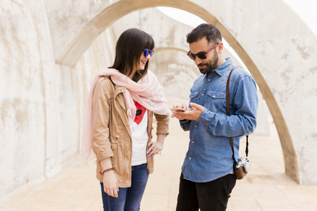 smiling-young-woman-looking-at-man-using-cell-phone_23-2147863507.jpg