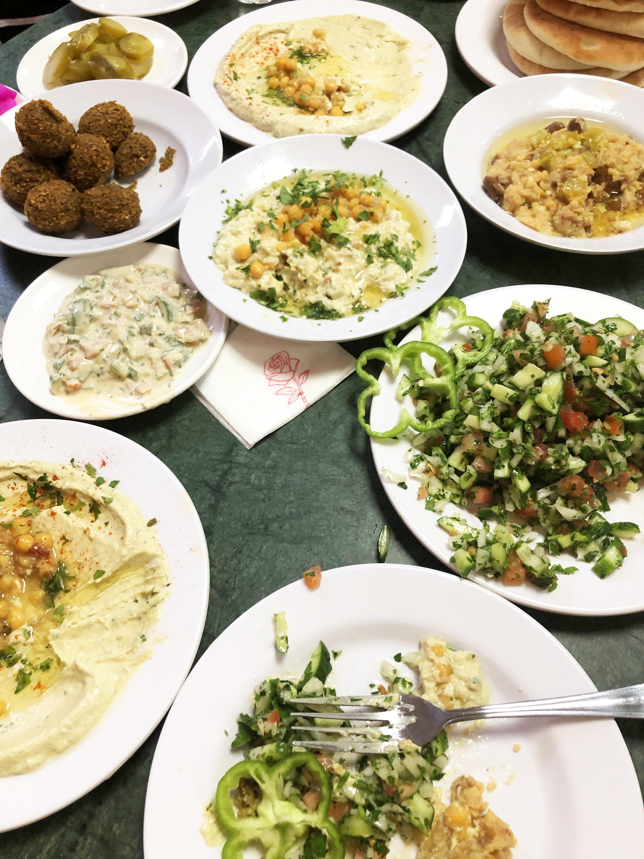 Traditional breakfast: vegetables, hummus, and falafel.